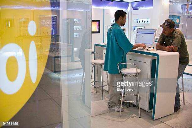 A patron speaks to a representative at an Oi mobile phone store in the Eldorado Mall in Sao Paulo Brazil on Thursday Dec 10 2009 Telemar Norte Leste...