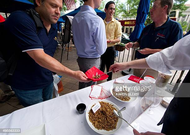 A patron takes a helping of roasted mealworms and roasted crickets on June 4 2014 during a global Pestaurant event sponsored by Ehrlich Pest Control...