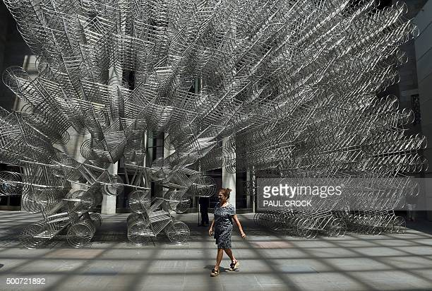 A patron walks past 'Forever bicycles' by Chinese artist and human rights activist Ai Weiwei following the launch of the joint exhibition 'Andy...