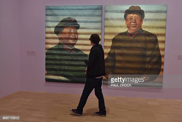 A patron walks past two portraits of Zedong by Chinese dissident artist Ai Weiwei following the launch of the joint exhibition 'Andy Warhol/Ai...