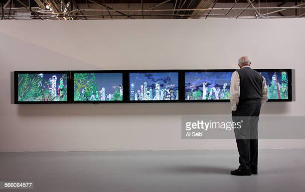 Patron watches the artwork by Chiho Aoshima from Tokyo, called City Glow: 2005; a five–channel DVD installation that is part of the exhibition...