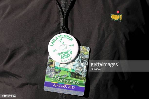 A patron wears an 'Arnie's Army' pin alongside a Masters badge during the first round of the 2017 Masters Tournament at Augusta National Golf Club on...