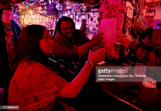 Patron who called himself Smooth Walker the Sweet Talker, right, and others, toast at The Alley on Grand Avenue Oakland, Calif., on Monday, March 16,...