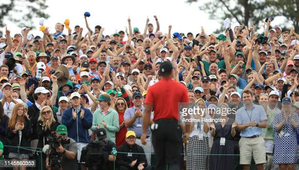 Patrons applaud Tiger Woods of the United States as he leaves the 18th green after winning the Masters at Augusta National Golf Club on April 14,...