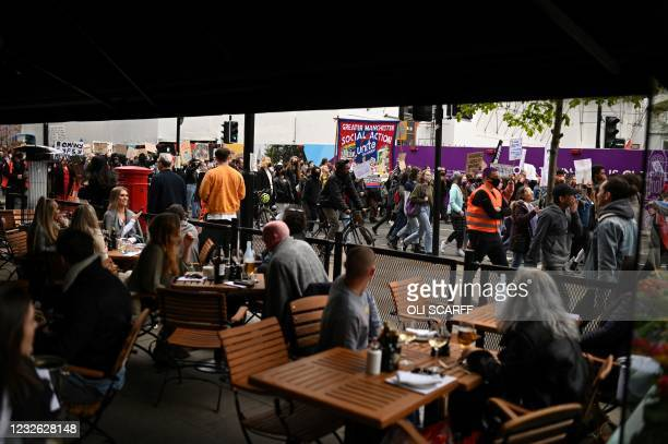 Patrons at a restaurant watch as demonstrators protesting against the Police, Crime, Sentencing and Courts Bill 2021 march in central Manchester on...