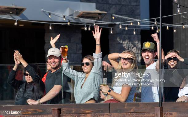 Patrons at Wild Goose Tavern in Costa Mesa cheer a group protesting the shutdown of businesses on Sunday, December 13, 2020.