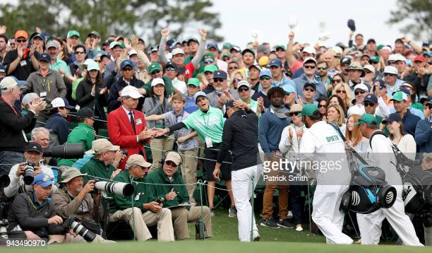 Patrons cheer as Jordan Spieth of the United States leaves the 18th green during the final round of the 2018 Masters Tournament at Augusta National...