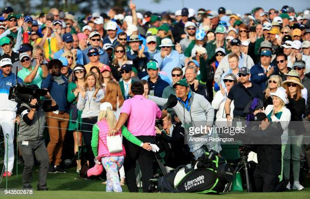 Patrons cheer as Patrick Reed of the United States and his wife Justine walk off the 18th green after his 15underpar 71 during the final round to win...