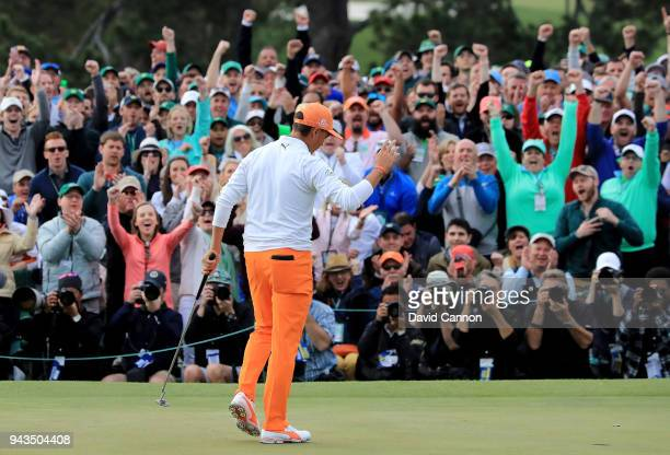 Patrons cheer as Rickie Fowler of the United States waves after putting on the 18th green during the final round of the 2018 Masters Tournament at...