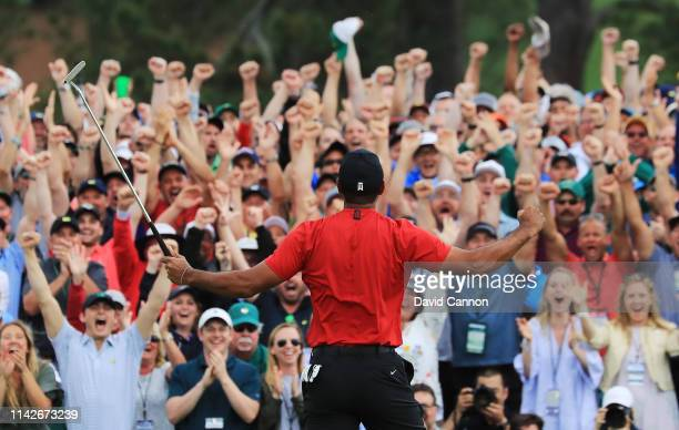 Patrons cheer as Tiger Woods of the United States celebrates after sinking his putt on the 18th green to win during the final round of the Masters at...