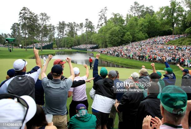 Patrons cheer as Tiger Woods of the United States celebrates his birdie on the 16th green during the final round of the Masters at Augusta National...