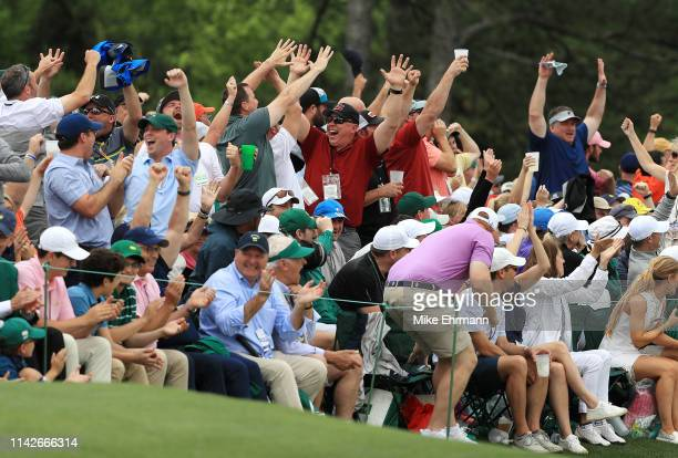 Patrons cheers after Tiger Woods of the United States sunk a putt for birdie on the 16th green during the final round of the Masters at Augusta...