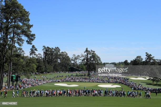 Patrons cross a walkway on the second fairway as Sergio Garcia of Spain and Charley Hoffman of the United States walk to the green during the third...