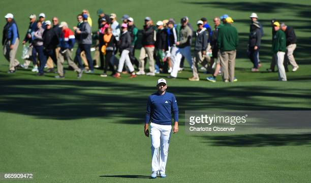 Patrons cross the second fairway as Sergio Garcia walks to the green during second round action of the Masters Tournament at Augusta National Golf...