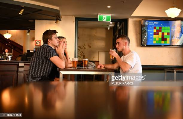 Patrons drink beer at a pub in the Rocks area of Sydney on June 1, 2020. - Social distancing regulations eased across Australia on June 1 with...