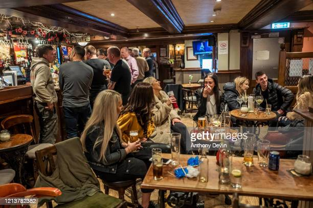 Patrons enjoy a last drink at closing time at The White House pub in Stalybridge on March 20, 2020 in Manchester, United Kingdom. British Prime...