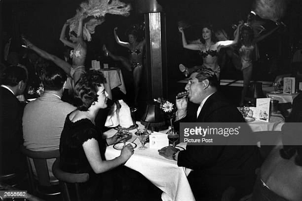 Patrons enjoy watching the dancers in a cabaret club. Original Publication: Picture Post - 8438 - Prosperity Story - unpub.