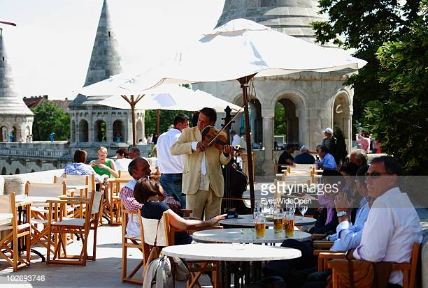Patrons listen to a musician in a restaurant at the Buda Castle on May 30 2010 in Budapest Hungary Budapest is a large european city and the...
