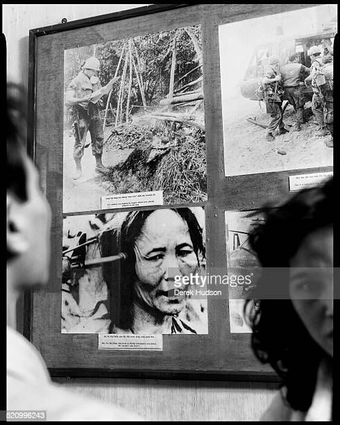 Patrons look at photographs of the My Lai massacre in an unidentified war museum Ho Chi Minh City Vietnam 1995 During the massacre hundreds of...