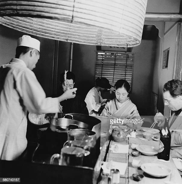 Patrons of a Tokyo restaurant eating tempura, seafood and vegetables dipped in batter and deep fried, Japan, circa 1955.
