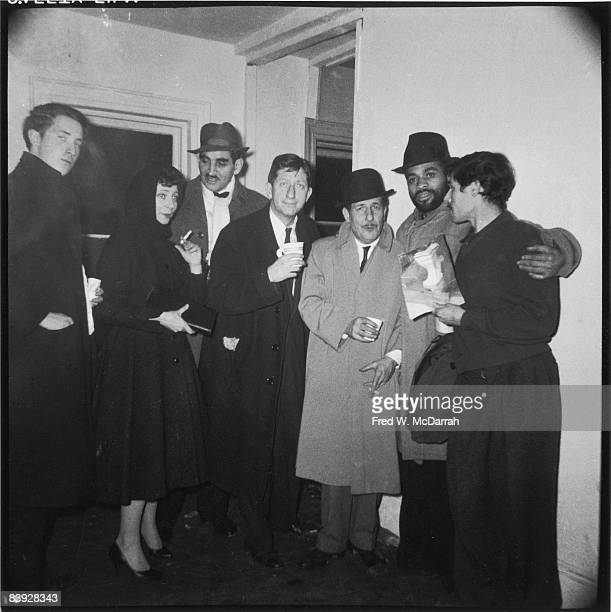 Patrons of Artist's Club apparently all in trenchcoats pose together at the club's New Year's Eve party New York New York December 31 1958 Pictured...