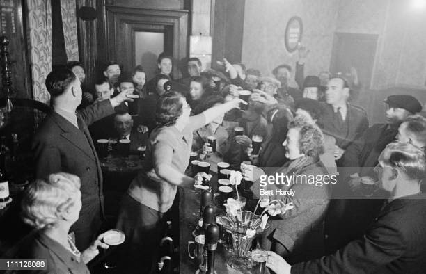 Patrons of The Crown public house on Blackfriars Road London celebrate the wedding of Princess Elizabeth and Philip Mountbatten Duke of Edinburgh...