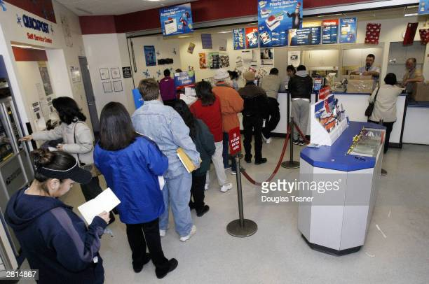 Patrons of the Gallup New Mexico Post Office stand in line waiting to mail there Christmas cards and packages December 16 2003 While yesterday is...