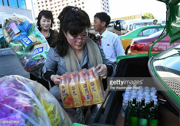 Patrons of the Kwangbok department / grocery store load plastic flowers and food into their trunk in Pyongyang North Korea on May 4 2016 The items...