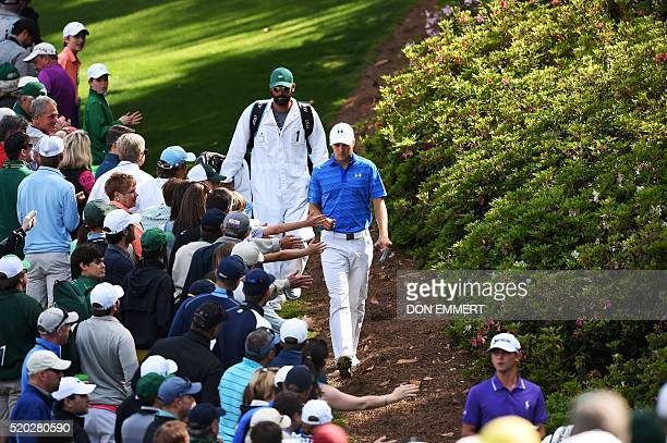 Patrons reach out to greet US golfer Jordan Spieth as he walks down to the 6th green during Round 4 of the 80th Masters Golf Tournament at the...