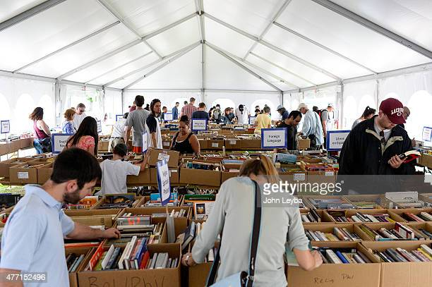 Patrons rummage through books under a big tent where the Denver Public Library held it's annual book sale June 15 2015 at the Denver Public Library