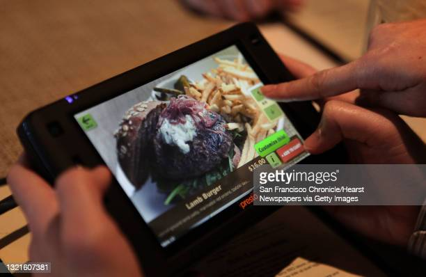 Patrons scrolling a new tablet that restaurants can put at every table for do-it-yourself ordering and paying the bill at Calafia in Palo Alto,...