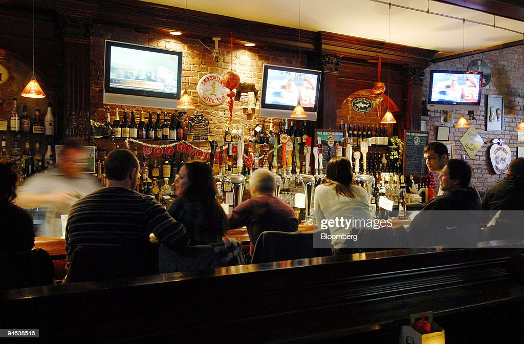 Patrons sit at the bar at the Downtown Bar and Grill in the : News Photo
