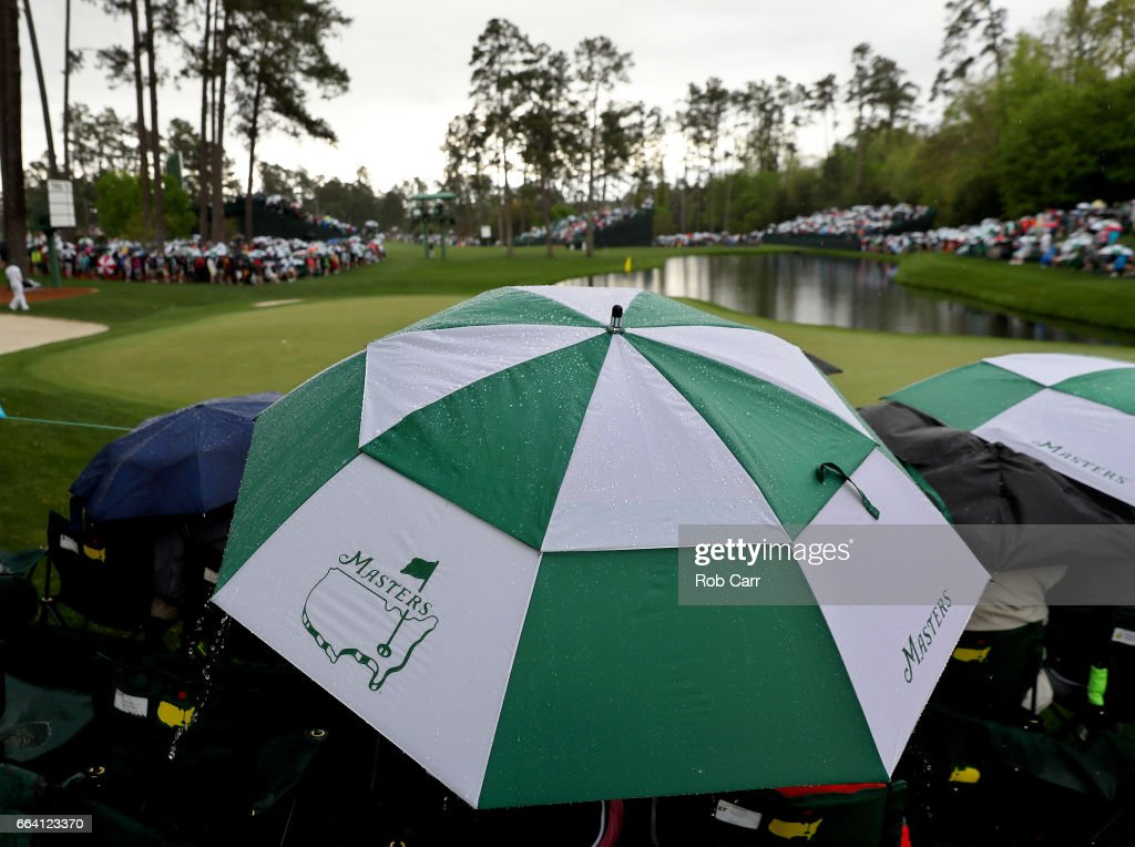 Patrons use an umbrealla next to the 16th green during a practice round prior to the start of the 2017 Masters Tournament at Augusta National Golf Club on April 3, 2017 in Augusta, Georgia.