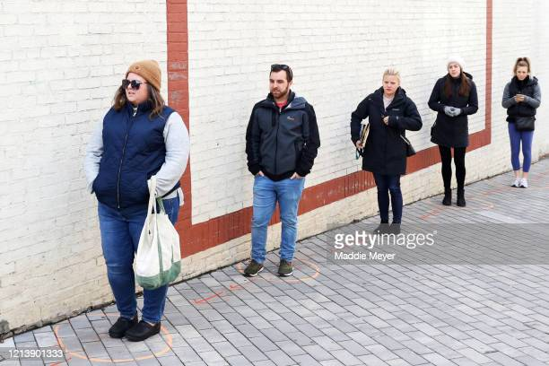 Patrons wait in line for the Safe Supply outdoor grocery store at Bow Market on March 21, 2020 in Somerville, Massachusetts. In order to comply with...