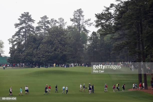 Patrons walk across the second fairway after play was suspended due to inclement weather during a practice round prior to the start of the 2017...