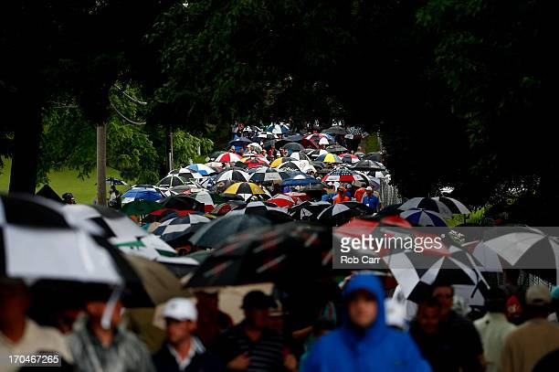 Patrons walk off the course after play was suspended due to weather during Round One of the 113th U.S. Open at Merion Golf Club on June 13, 2013 in...