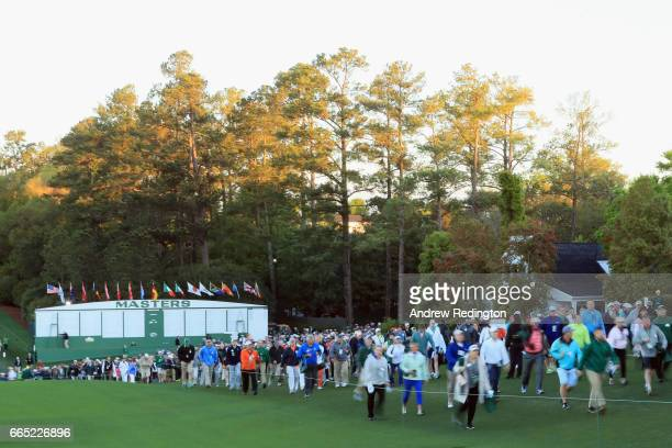 Patrons walk onto the course next to the first fairway prior to the start of the first round of the 2017 Masters Tournament at Augusta National Golf...
