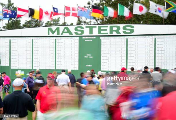 Patrons walk past a leaderboard next to the first fairway during a practice round prior to the start of the 2017 Masters Tournament at Augusta...