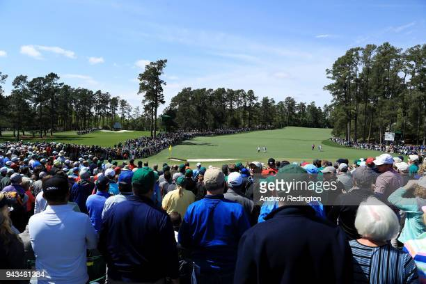 Patrons watch as Rory McIlroy of Northern Ireland caddie Harry Diamond Patrick Reed of the United States and caddie Kessler Karain walk together on...