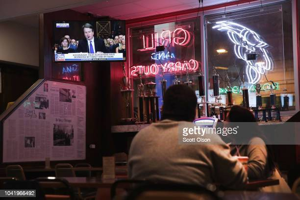 Patrons watch as the television at the Billy Goat Tavern plays live the Senate Judiciary Committee hearing on Capitol Hill where professor Christine...