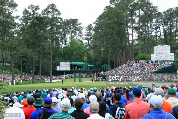 Patrons watch as Tiger Woods of the United States putts on the 15th green during the final round of the Masters at Augusta National Golf Club on...