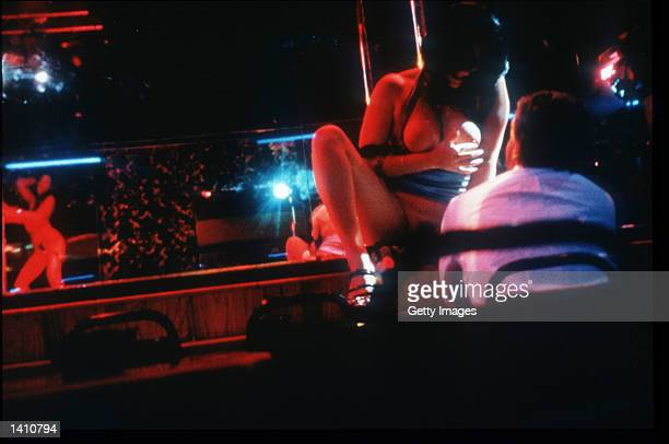 Patrons watch exotic dancers in a sex club May 10 1998 in New York City Business continues at topless clubs strip clubs and other sex clubs as owners...