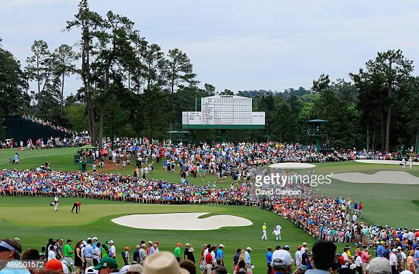 Patrons watch the group of Tiger Woods of the United States and Rory McIlroy of Northern Ireland on the second green during the final round of the...
