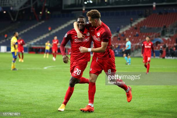 Patson Daka of RB Salzburg celebrates with teammate Mergim Berisha after scoring his sides third goal during the UEFA Champions League PlayOff second...