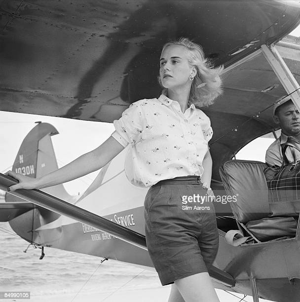Patsy Pulitzer leaning against a seaplane belonging to the Everglades Flying Service at Palm Beach Florida circa 1955