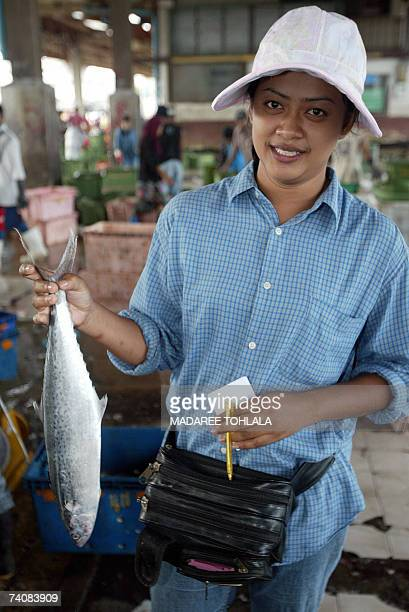 A Thai dealer display a fish at a fishing market in Thailand's restive southern Pattani province 06 May 2007 The central bank last month cut its key...