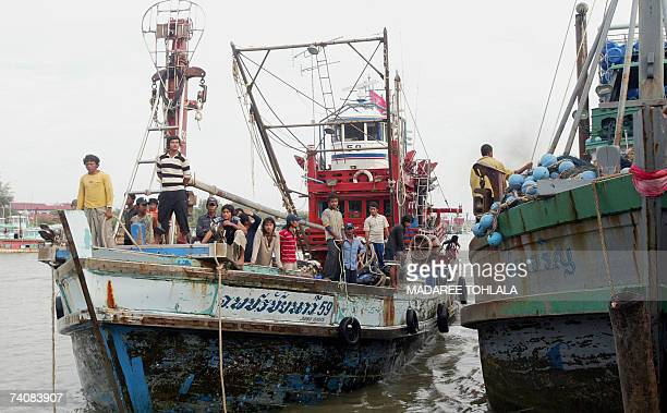 Fishermen mostly from neighbouring Myanmar and Cambodia in a boat approach to the port with their catch of the day in Thailand's restive southern...