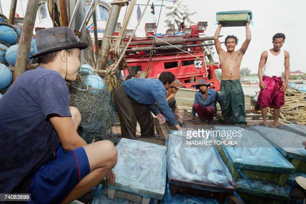 Fishermen mostly from neighbouring Myanmar and Cambodia offload their catch of the day from boat at Thailand's restive southern Pattani fishing port...