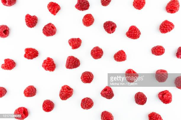 pattern made from fresh raspberries, top view, flat lay pattern, isolated on a white background. - raspberry stock pictures, royalty-free photos & images