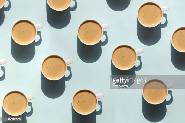 pattern made of cup of cappuccino on blue background - coffee break stock pictures, royalty-free photos & images